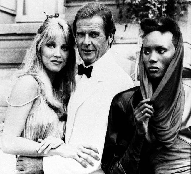 In this Aug. 17, 1984 file photo, actor Roger Moore, alias British secret agent James Bond, is seen with his co-stars Tanya Roberts, and Grace Jones, right, in front of Chateau de Chantilly, on the set of the 007 action film
