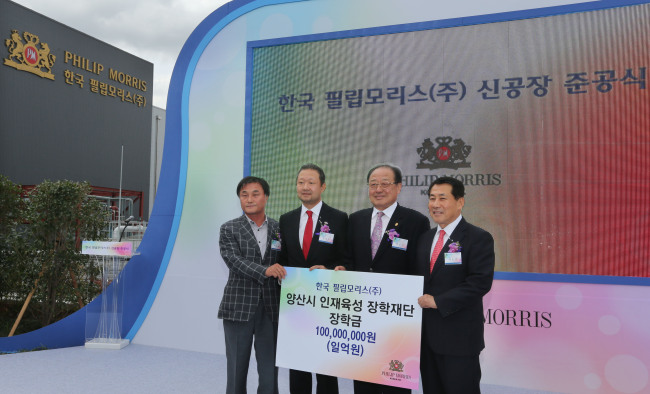 Chong Il-woo (second from left), managing director of PMKI, delivers 100 million won in scholarship funds to a charity foundation during the opening ceremony for its new plant in Yangsan, South Gyeongsang Province, Monday. (Philip Morris Korea)