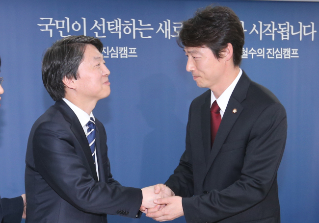 Independent presidential candidate Ahn Cheol-soo (left) shakes hands with Rep. Song Ho-chang at his campaign headquarters in Seoul on Tuesday. (Yonhap News)