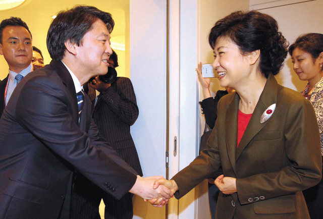 Saenuri Party presidential nominee Rep. Park Geun-hye shakes hands with independent candidate Ahn Cheol-soo at a forum in Seoul on Tuesday. (Yonhap News)