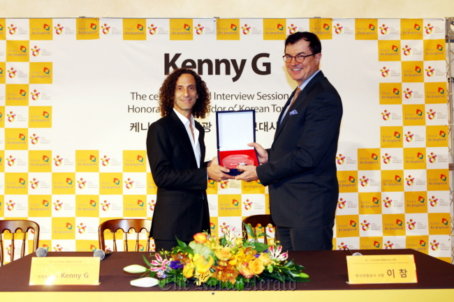 Jazz saxophonist Kenny G (left) and The Korea Tourism Organization CEO Lee Charm pose for a photo holding a plaque given to Kenny G, who was named an honorary ambassador of Korea tourism on Wednesday in Seoul. (The Korea Tourism Organization)