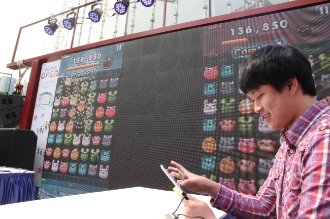 """A player shows off his skills in an """"Anipang"""" mobile game compeition in front of Lotte Department Store in Seoul earlier this month. (Yonhap News)"""