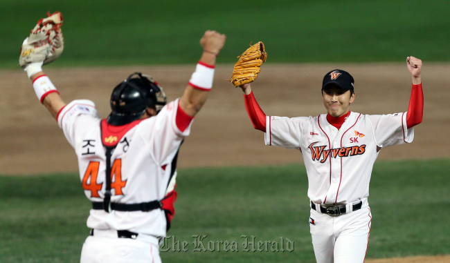 The SK Wyverns` pitcher Jung Woo-ram (right) cheers with catcher Cho In-sung after their team beat the Lotte Giants6-3 to reach the championship final on Monday in Incheon. (Yonhap News)