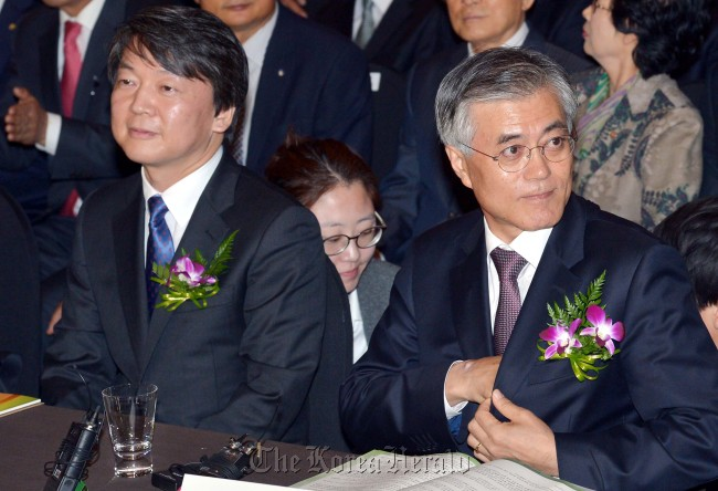 Independent presidential candidate Ahn Cheol-soo (left) takes his seat next to the Democratic United Party's presidential candidate Moon Jae-in at a meeting for small retailers in Seoul on Tuesday. (Park Hyun-koo/The Korea Herald)