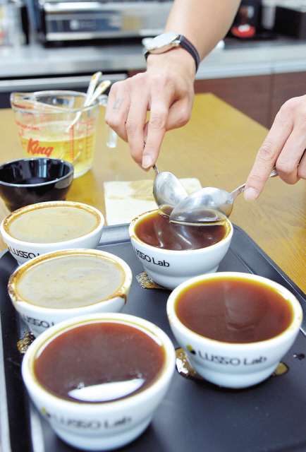 During the coffee cupping process, one must first skim the grounds off the surface with two spoons and discard before tasting as demonstrated above at the Lusso Lab Academy in Seoul. (Kim Myung-sub/The Korea Herald)