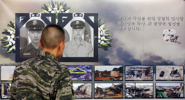 A soldier looks at pictures of soldiers killed during North Korea's artillery attack on Yeonpyeongdo on Nov. 23, 2010, in an exhibition to mark its second anniversary, at Gimpo Airport, Tuesday. (Yonhap News)