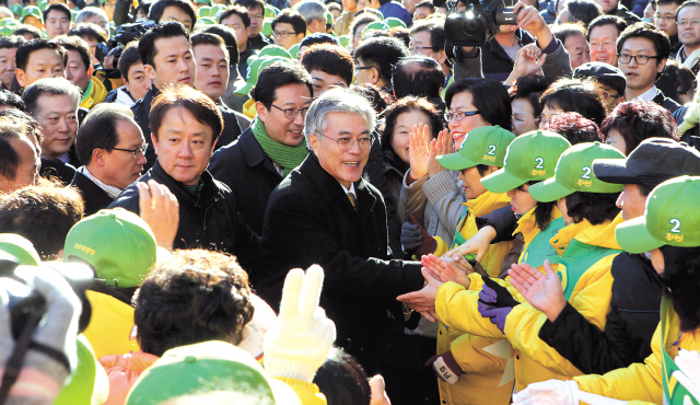 Democratic United Party presidential candidate Moon Jae-in (center) shakes hands with supporters in Busan on Tuesday. (Ahn Hoon/The Korea Herald)