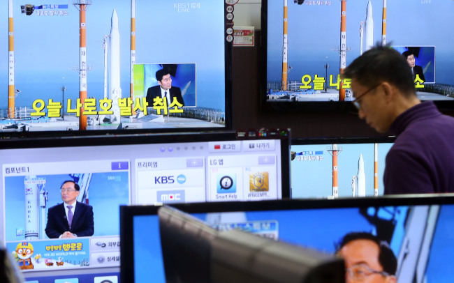 A man at an electronics shop in Yongsan, Seoul, watches TV news reports about the cancellation of the Naro space rocket's launch due to a technical problem on Thursday afternoon. (Yonhap News)
