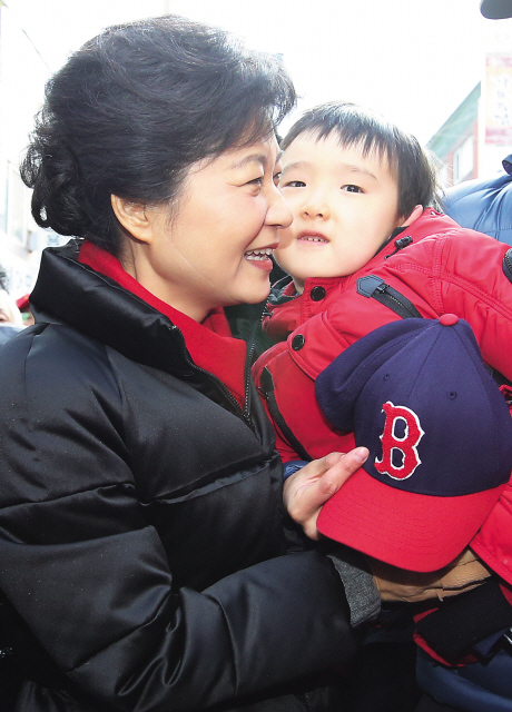 Saenuri Party presidential candidate Park Geun-hye (left) holds a child as she meets with the residents during a visit to Injae, Gangwon Province, Sunday. (Yonhap News)