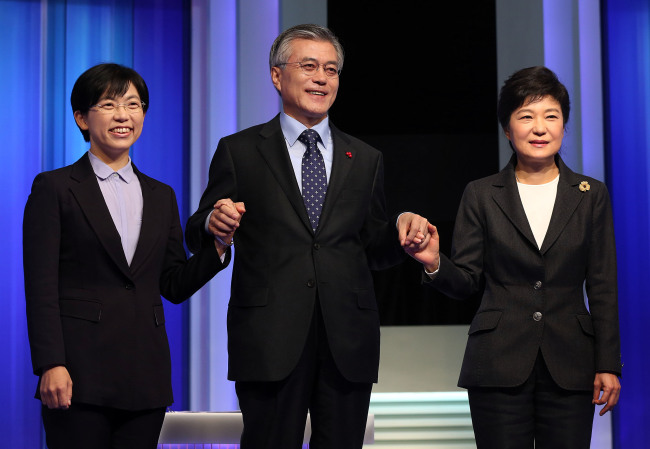 Presidential candidates Park Geun-hye (from right) of the Saenuri Party, Moon Jae-in of the Democratic United Party and Lee Jung-hee of the Unified Progressive Party clasp hands ahead of the first of their three television debates on Tuesday. (National Assembly photo pool)