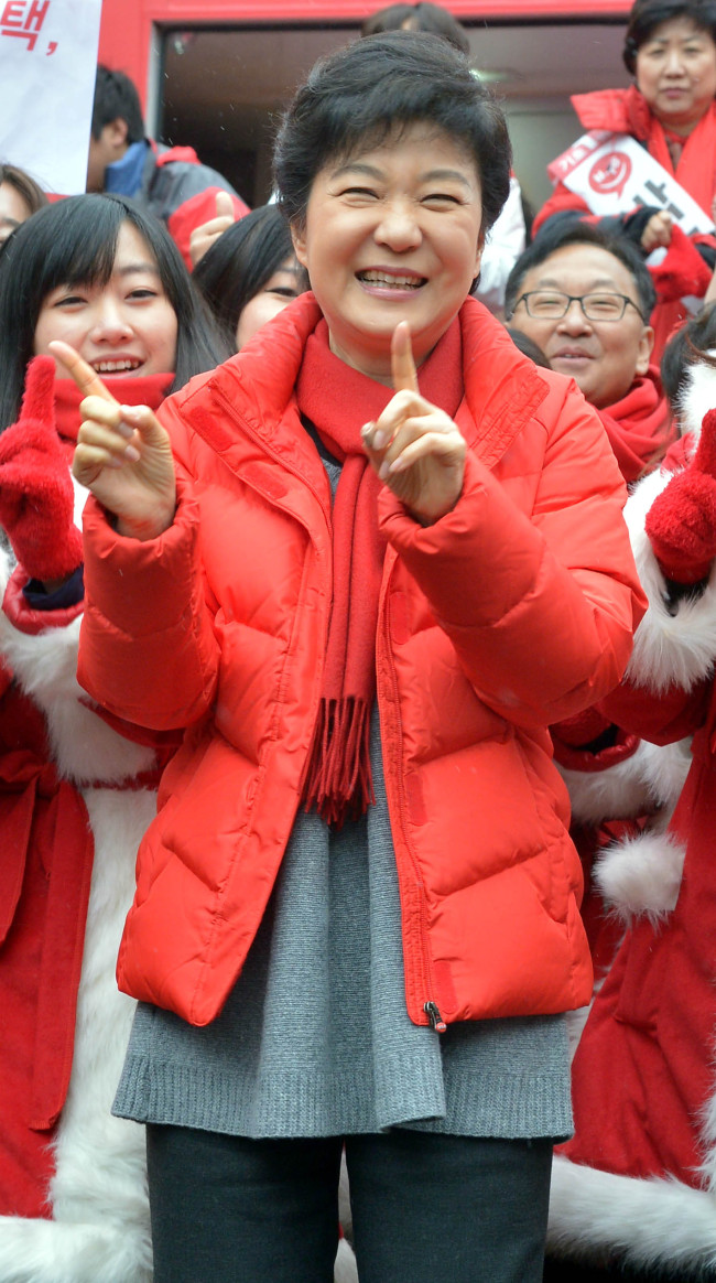 Saenuri Party candidate Park Geun-hye dances with campaign supporters at a market in southern Seoul on Friday. (Park Hyun-koo/The Korea Herald)