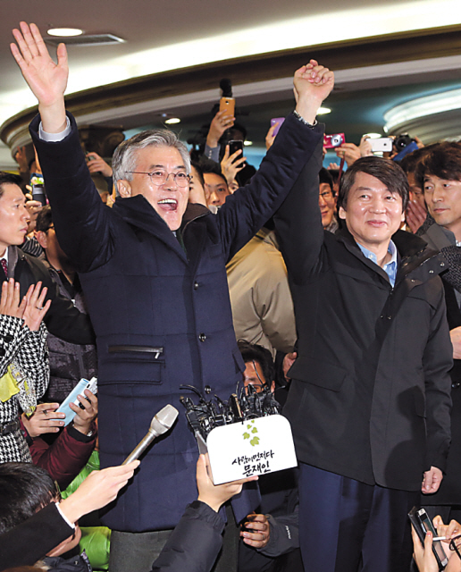 DUP candidate Moon Jae-in (left) and Ahn Cheol-soo raise their arms at their first joint campaign event in Busan on Friday. (Yonhap News)
