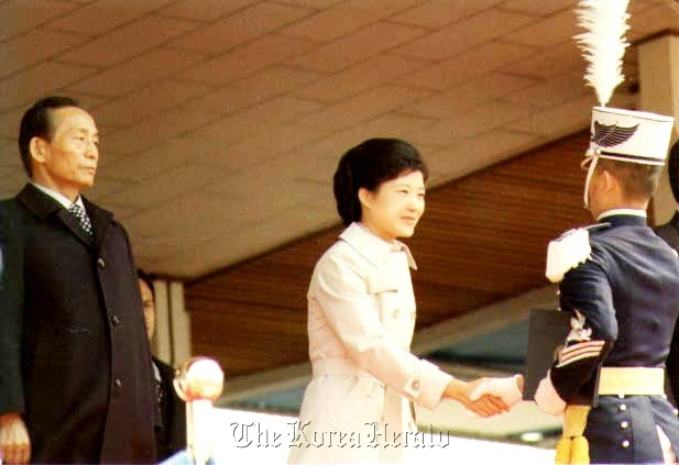 Park Geun-hye (center) shakes hands with a military cadet as she stands in for late first lady Yook Young-soo.