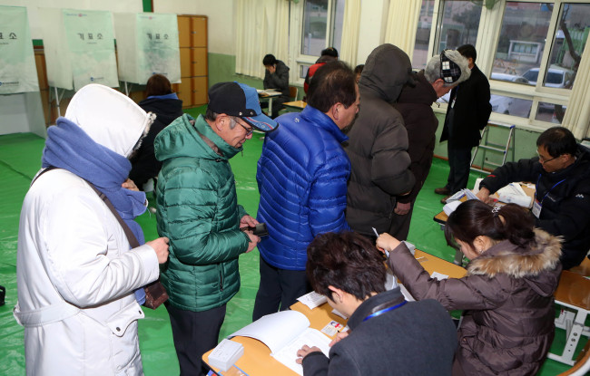 Voters stand in a queue to cast their ballots at a polling station in Busan. (Yonhap News)