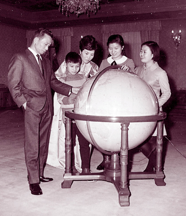 (From left) Late former President Park Chung-hee, first lady Yook Young-soo (back)and children Ji-man, Geun-hye and Geun-ryeong look at a globe in the Blue House.