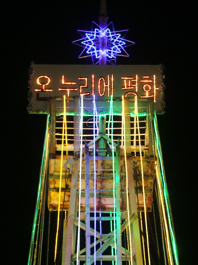 A Christmass tree-shaped tower near South Korea's western border with North Korea is lit by a Christian group on Dec. 22. (Yonhap News)