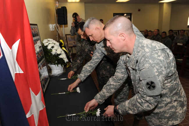 Lt. Gen. John D. Johnson (center) and his fellow troops lay chrysanthemums in front of the photos of the deceased 46 sailors of the ill-fated warship Cheonan during a memorial ceremony held at the Warrior Base on Friday. ( EUSA)