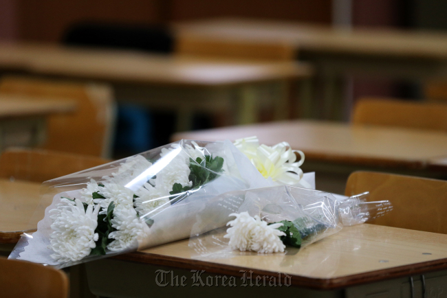 Flowers are laid on the desk of a teenage student who killed himself after being bullied at school in Gyeongsan, North Gyeongsang Province, on March 11. (Yonhap News)