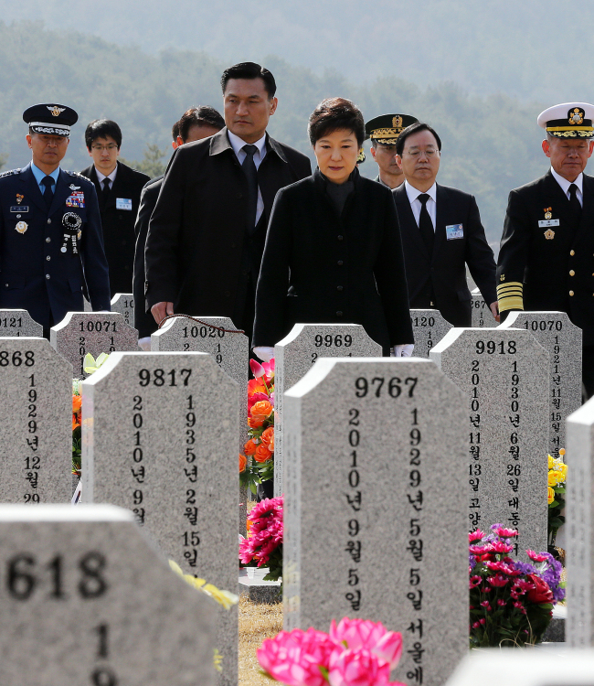 President Park Geun-hye walks to the grave of Han Joo-ho, the chief warrant officer who died during a search and rescue operation, at Daejeon National Cemetery ahead of the event marking the third anniversary of the sinking of the South Korean warship Cheonan on Tuesday. (Yonhap News)