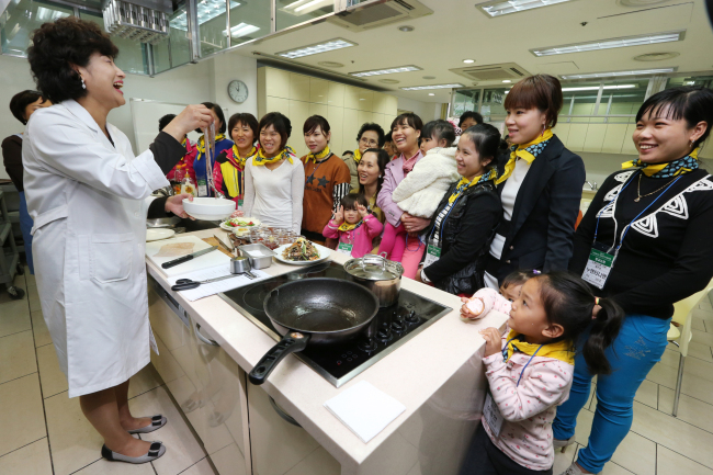 Immigrant spouses and their children from Boseung and Gangjin, South Jeolla Province, attend a cooking class on Korean traditional food held at Sookmyung Women's University in Seoul on March 29. (Yonhap News)