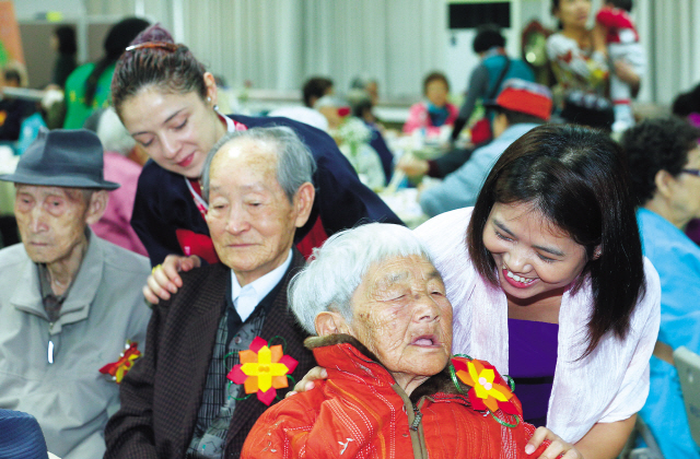 Immigrant spouses give seniors a shoulder massage at a welfare program held at a district office in Gwangjin-gu, Seoul on April 9. (Yonhap News)