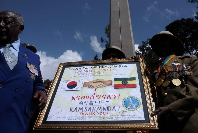 Ethiopian Korean War veterans hold a framed commemoration poster during an event held in Addis Ababa, Ethiopia, Saturday, to reenact Ethiopian troops' departure for South Korea to fight the war. (Yonhap News)