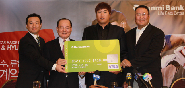 South Korean pitcher Ryu Hyun-jin (right) poses with Jay S. Yoo, chief executive of Hanmi Bank, after signing a contract to appear on the bank's commericals on Monday in Los Angeles. (Yonhap News)