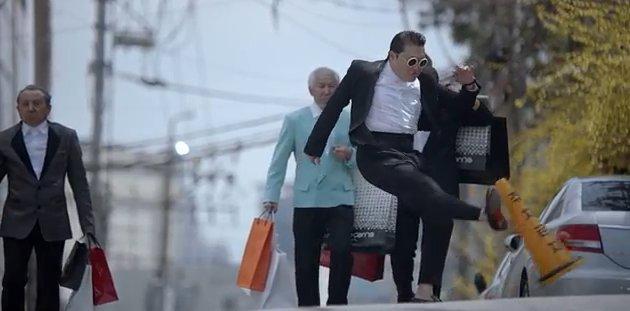 "A screen capture of Psy's ""Gentleman"" music video scene where he kicks a traffic cone."
