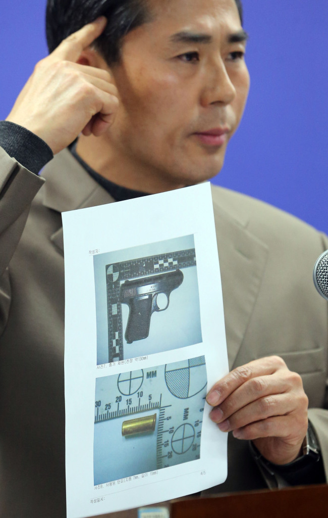 A police chief detective shows images of a pistol and bullet shell used in a suicide case which occurred in Yeongdeungpo-gu, Seoul, on April 12. (Yonhap News)