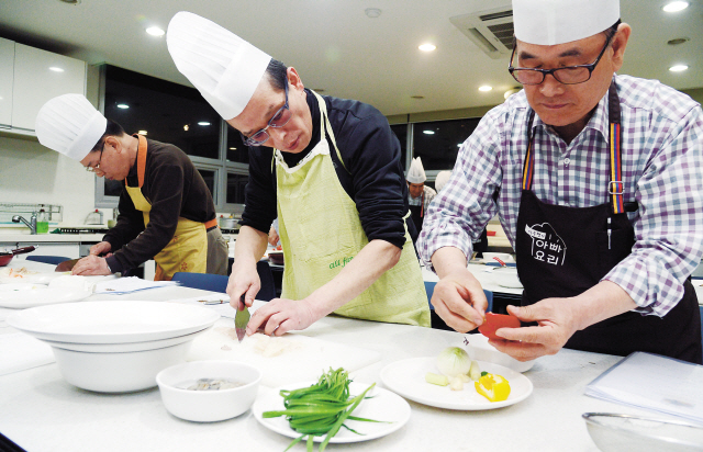 Participants learn to cook at the male-only Daddy's Cooking Class at the Long Learn Academy in Gaepo-dong, Seoul, on Monday. (Ahn Hoon/The Korea Herald)