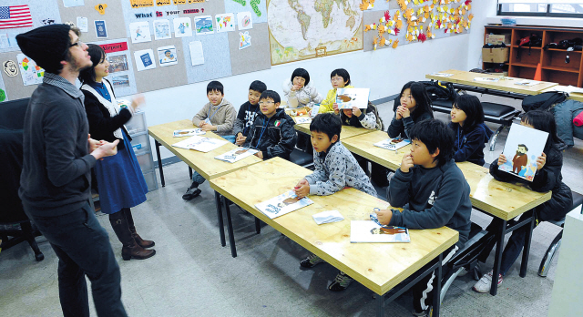 Elementary school students attend a class led by a native English teacher. (The Korea Herald file)