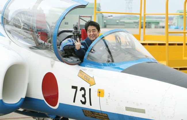 Japanese Prime Minister Shinzo Abe poses inside a Japanese military training jet at an air base in Miyagi prefecture on Sunday. The number 731 on the jet evokes Unit 731, a chemical and biological research unit of the Japanese Army that carried out lethal human experiments on prisoners of war during World War II. (AFP-Yonhap News)