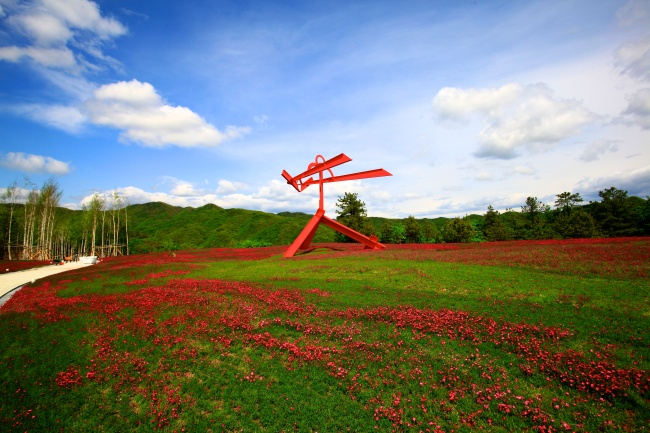"Mark di Suvero's red steel sculpture ""For Gerard Manley Hopkins"" stands in the flower garden. (Hansol Museum)"