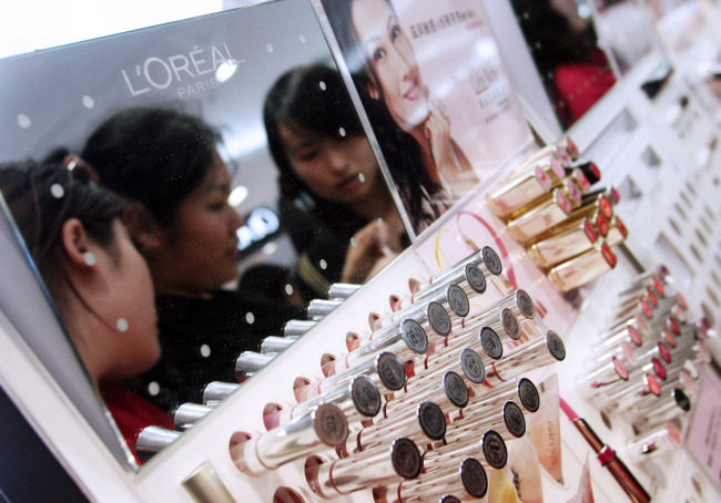 Young Chinese women try out the testers at a L' Oreal SA cosmetics counter at a shopping mall in Beijing. (Bloomberg)