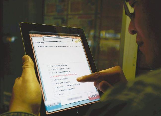 A man answers a DPJ survey on an iPad. (The Japan News)
