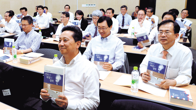 Participants of Seoul National College of Humanities' Ad Fontes Program hold up their textbooks during a class on Tuesday. (Park Hyun-koo/ The Korea Herald)