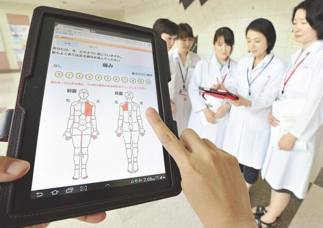 A tablet computing device for home-based cancer patients is shown at the National Cancer Center's Hospital East in Kashiwa, Chiba prefecture, Japan. (The Japan News)