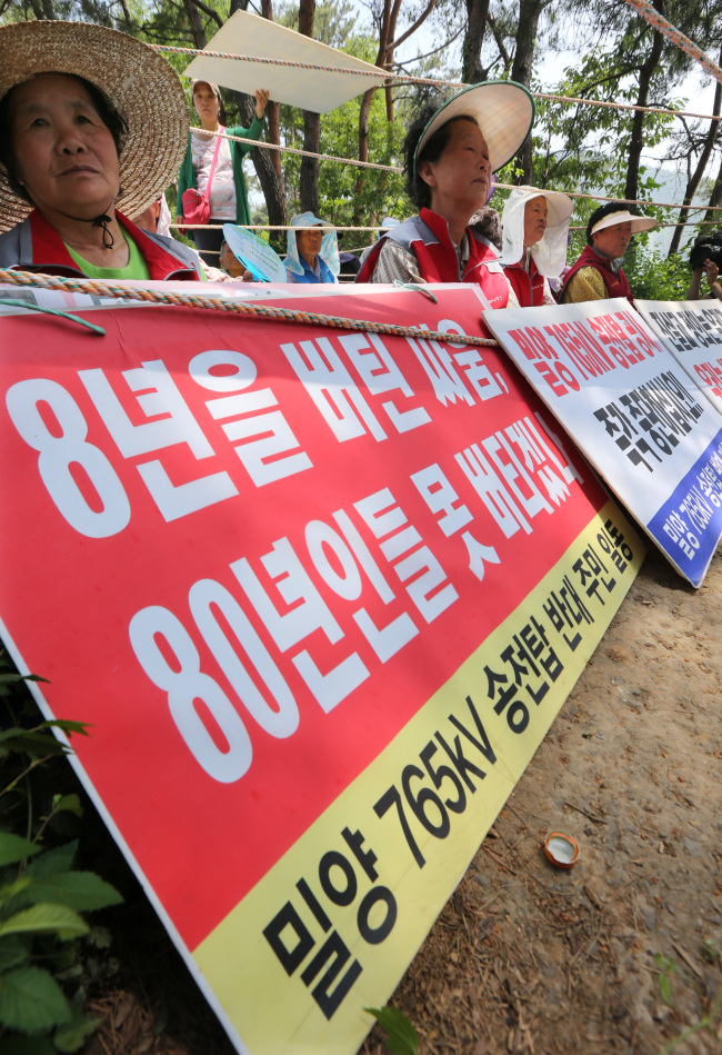 Residents stage a sit-in against the construction of high-voltage transmission towers in Miryang, South Gyeongsang Province, Friday. (Yonhap News)