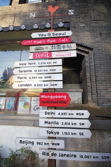 Signs posted on a pole outside the entrance of Seoul Selection Bookshop point out the direction and distance of major international cities. (Seoul Selection)