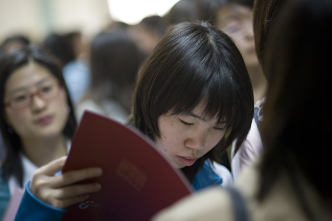 Attendees of a job fair sponsored by Beijing Technology and Business University wait to speak with a recruiter in Beijing. (Bloomberg)
