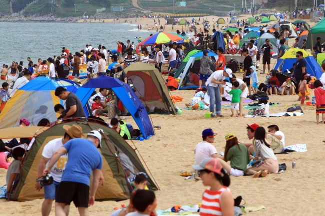 Holidaymakers enjoy the sun at the beach in Sokcho, Gangwon Province. (Yonhap News)