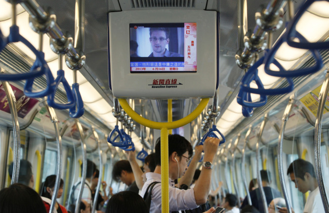 A TV screen shows the news of Edward Snowden, a former CIA employee who leaked top-secret documents about sweeping U.S. surveillance programs, in an underground train in Hong Kong Sunday. (AP-Yonhap News)