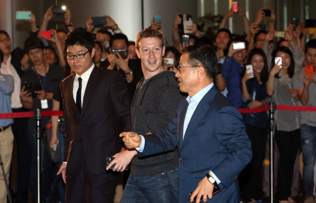 Mark Zuckerberg (center), one of the cofounders of Facebook, walks into Samsung Electronics' building in southern Seoul on Tuesday to meet with executives of the Korean tech giant. (Yonhap News)