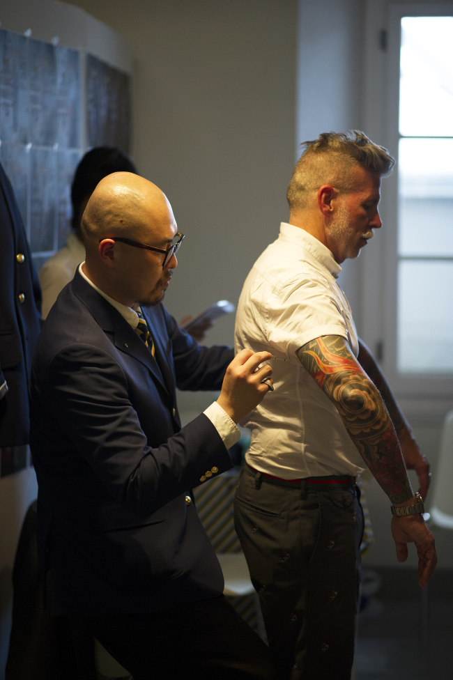 Ji Il-geun, head designer of menswear brand Instantology, makes a fit adjustment for celebrated buyer Nick Wooster. (Korea Creative Content Agency)