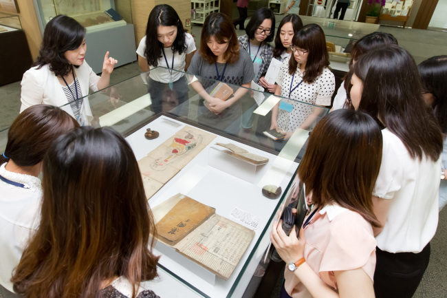 "Students look at the original copy of ""Dongui Bogam,"" a book about traditional Korean medicine published 400 years ago, at the National Museum of Korea on Monday. (Yonhap News)"