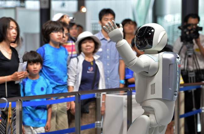 Honda Motor's humanoid robot Asimo interacts with visitors at the National Museum of Emerging Science and Innovation in Tokyo on Wednesday. (AFP-Yonhap News)