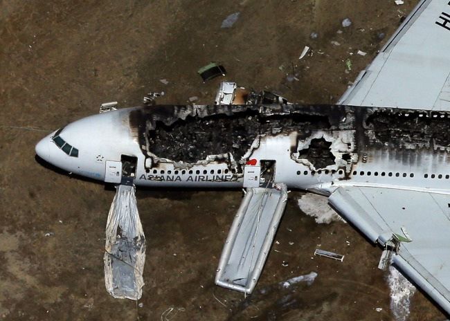 A Boeing 777 airplane lies burned on the runway after it crash landed at San Francisco International Airport July 6 in San Francisco, California. An Asiana Airlines passenger aircraft coming from Seoul, South Korea crashed while landing. There has been at least two casualties reported. (AFP)