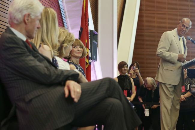 Fashion designer Oscar de la Renta (right) looks toward former President Bill Clinton (left) as he speaks at the Clinton Presidential Library in Little Rock, Arkansas, Monday. (AP-Yonhap News)