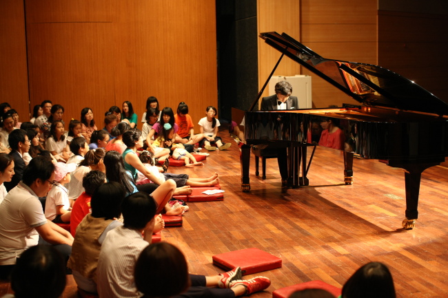 Audience members listen to pianist Kim Tae-hyung's performance at Gimjae Cultural Arts Center in July 2012. (The House Concert)