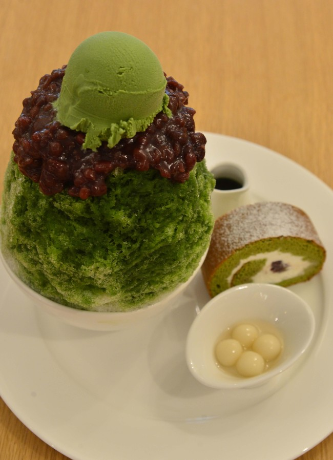 La Pomme's green tea kakigori for two features a dome of shaved ice in matcha syrup, topped with housemade red beans and matcha ice cream. (Lee Sang-sub/The Korea Herald)